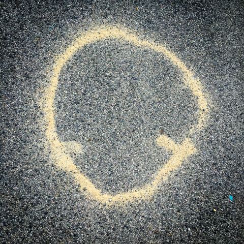 random wind-generated sand swirl on asphalt or reserved parking for spaceship?