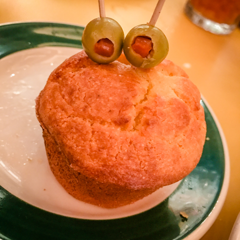 1. bake, buy or order a corn muffin 2. Place a toothpick skewered olive into the top 3. for added fun, use two skewered olives with pentimentos